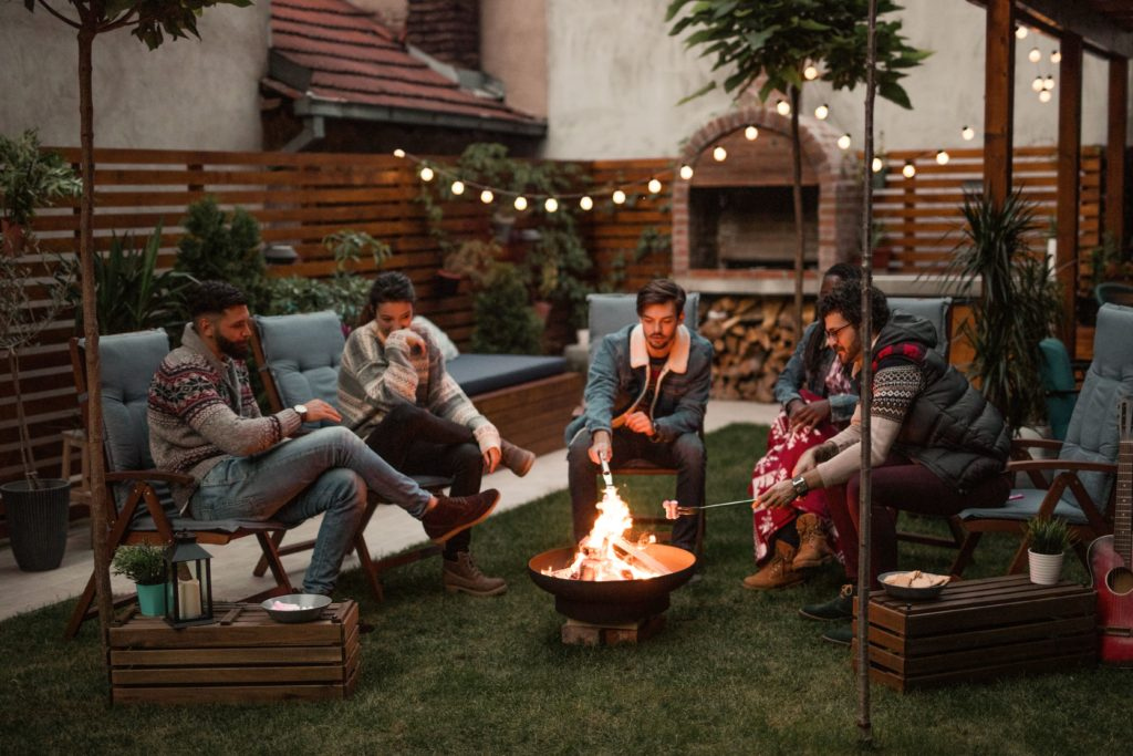 Group of friends gathered in backyard around fire pit