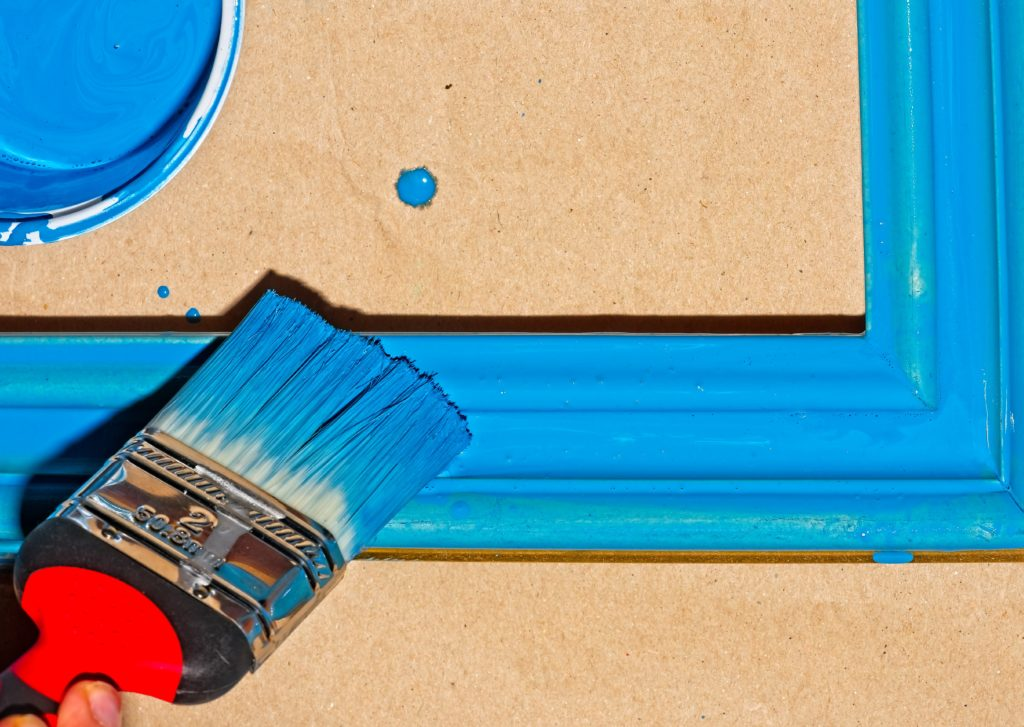 Closeup of a hand painting a picture frame blue