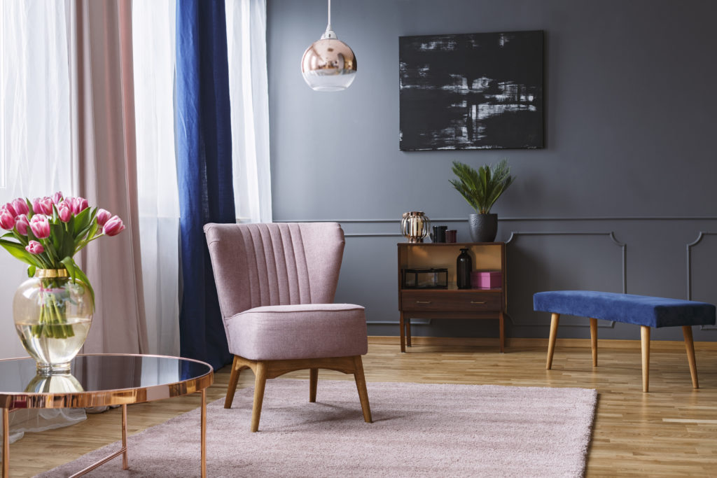 Pink armchair standing on a rug and under a lamp in living room with gray walls