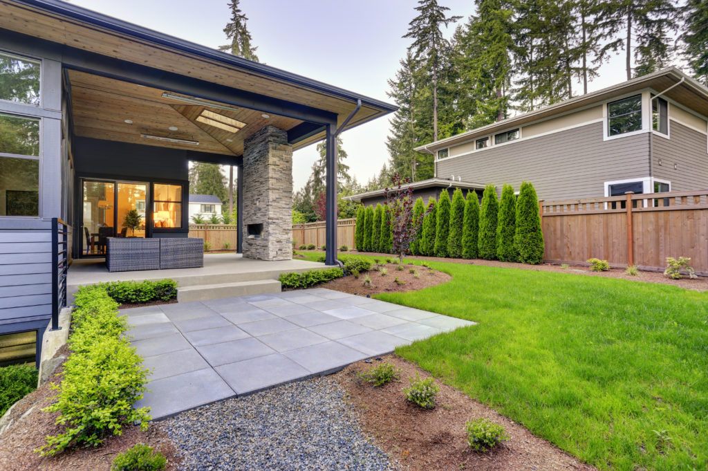 Modern backyard with paved patio and grassy area