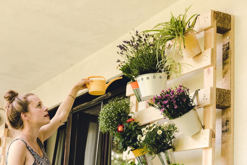 Young Woman Watering Flowers On Balcony