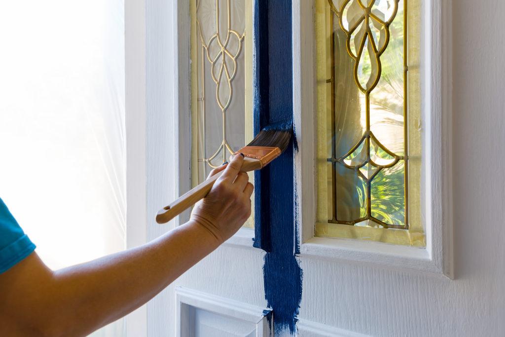 Woman paints her front door blue