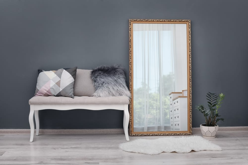 A full length mirror painted burnished gold