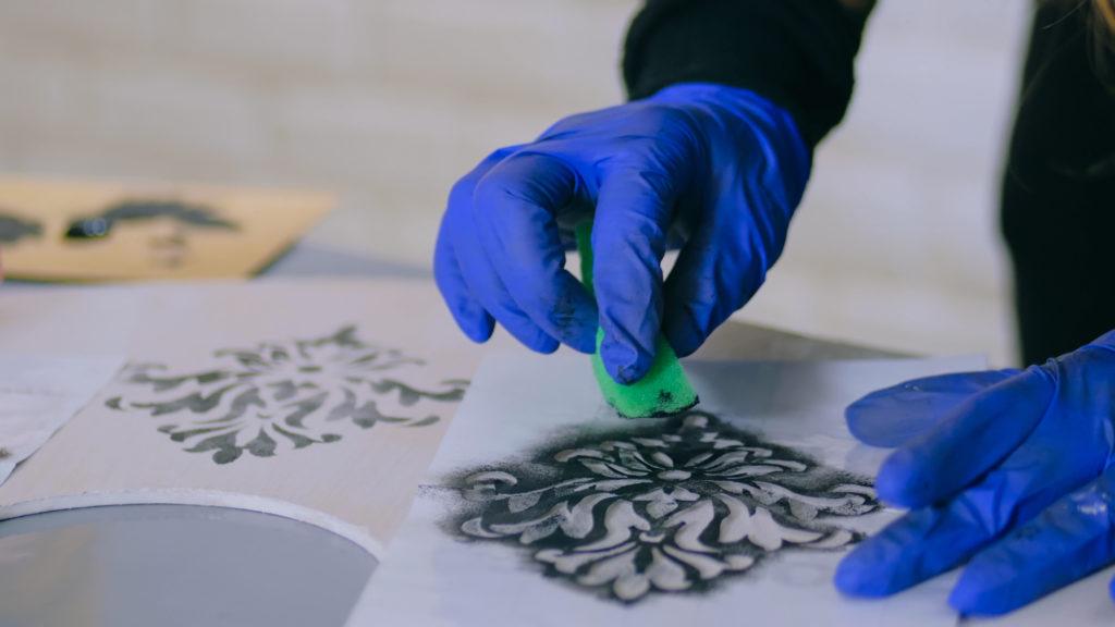 A woman paints bathroom tile with a stencil