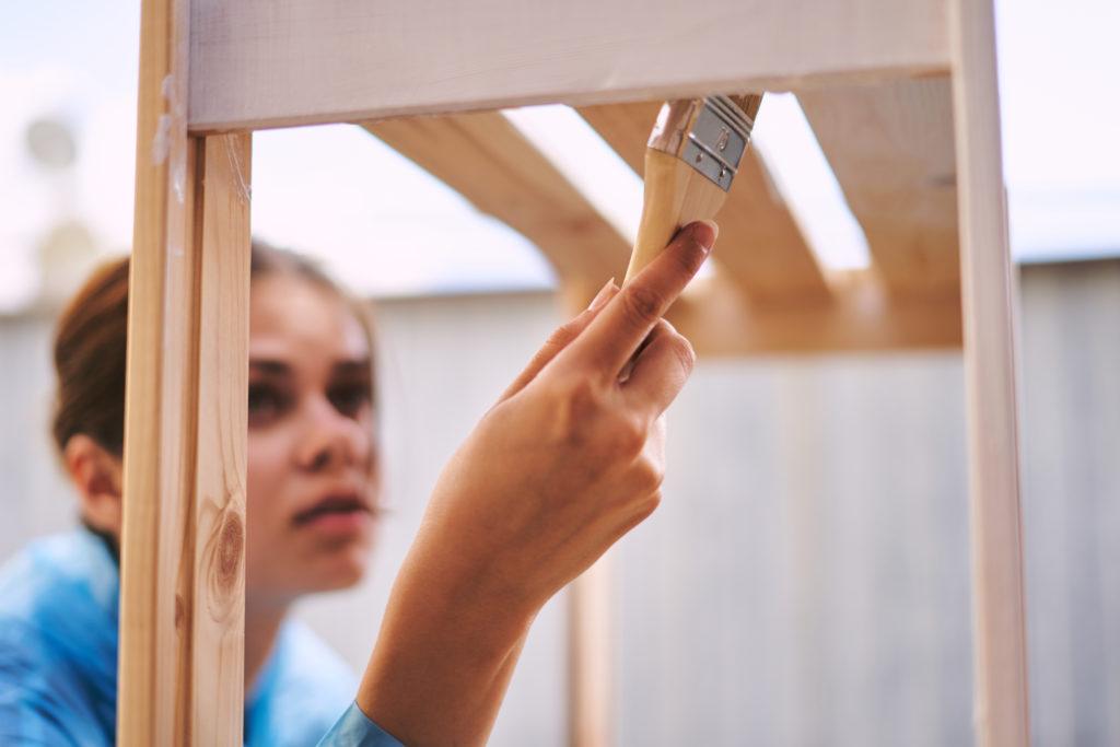 Woman painting bookshelves