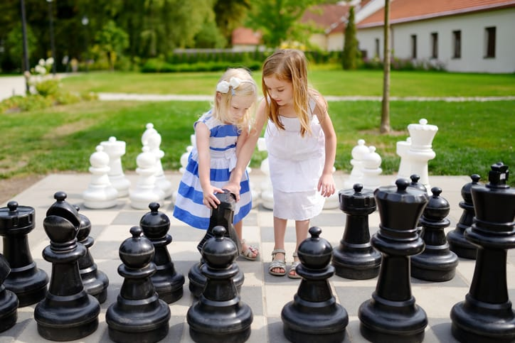 Two little sisters playing giant chess