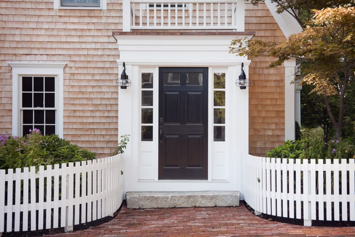 Entryway of brick New England home with picket fence