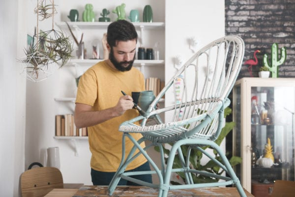 Bearded man painting a chair with milk paint
