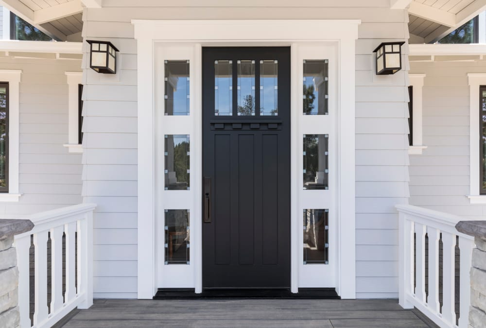 Black front door with white frame and white siding