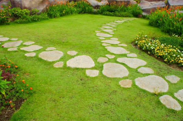 Stepping stones of various sizes leading to a garden