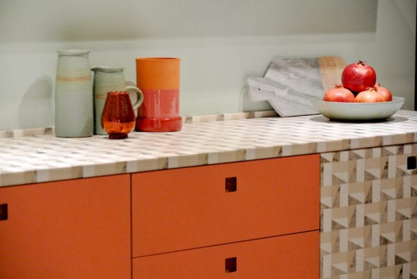 Coral kitchen cabinets with geometric pattern