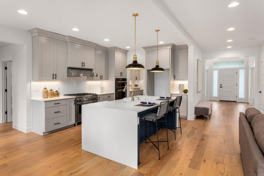 Luxury kitchen with greige cabinets and hardwood floors