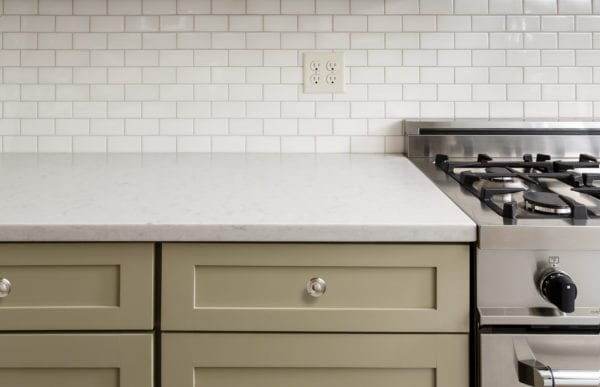 Kitchen counter with subway tile, stainless steel oven, and khaki green cabinets