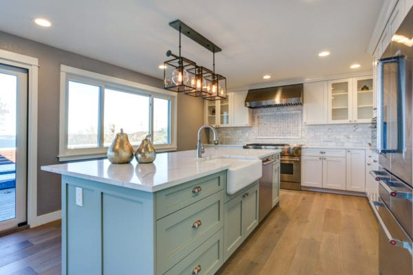 Kitchen with mint green island and stainless steel appliances