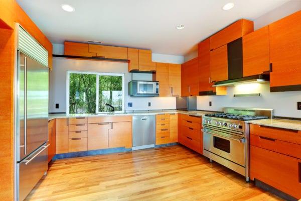 Modern kitchen with orange cabinets and steel appliances