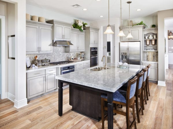 Luxury kitchen with stools at island and warm gray cabinets