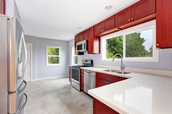 Kitchen with wine red cabinets and stainless steel appliances