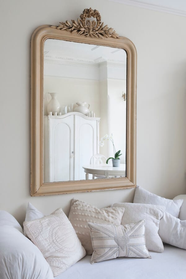Room with white decor and gold mirror that makes the room look bigger