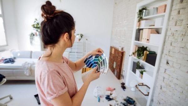 Woman choose paint color for shelves