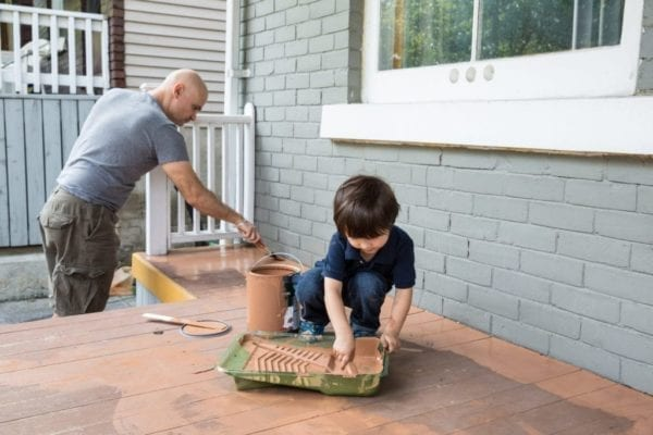 Father and son working together to paint the front porch