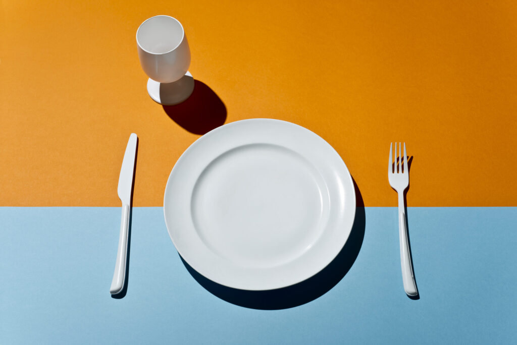 High Angle View Of white glass, fork, knife and plate on a colored table